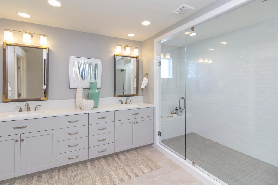This spa-inspired primary bath features sleek tile accents and a deluxe walk-in shower