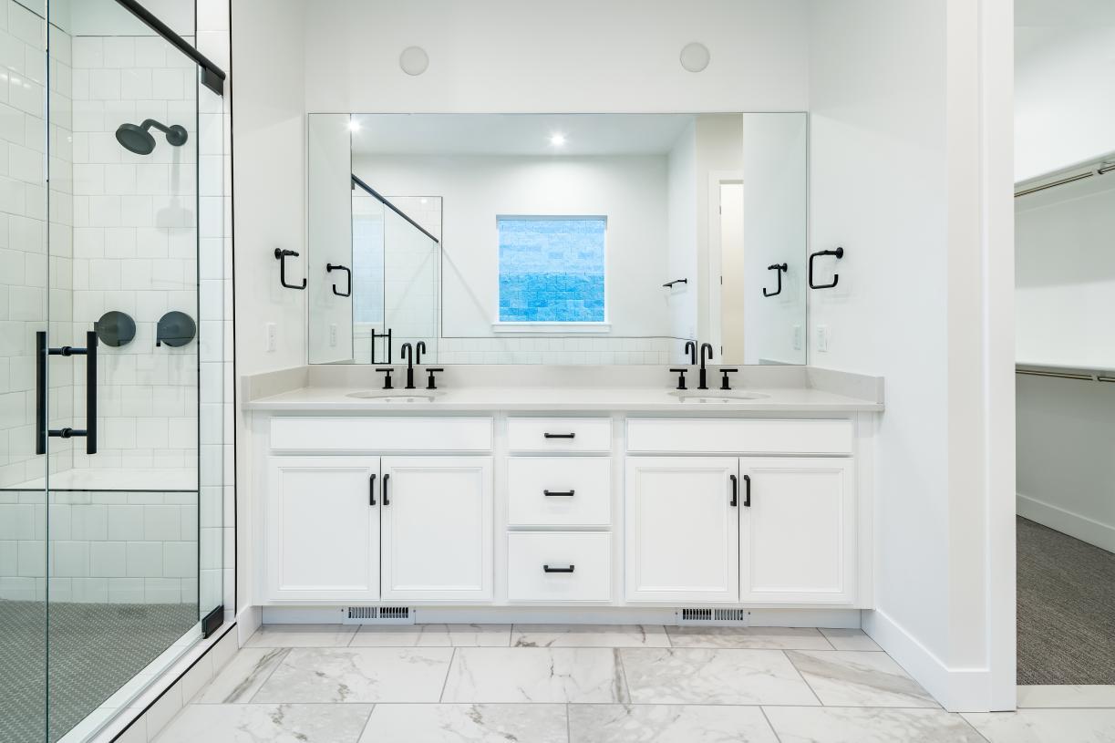 Beautiful primary bathroom with dual sink vanity, tile flooring, and walk-in closet