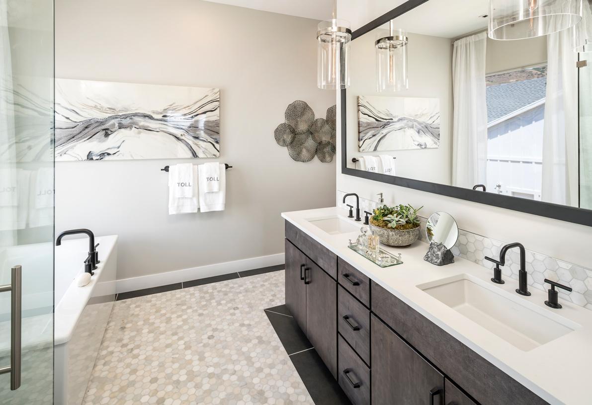 Lavish primary bathroom with dual-sink vanity and large freestanding soaking tub