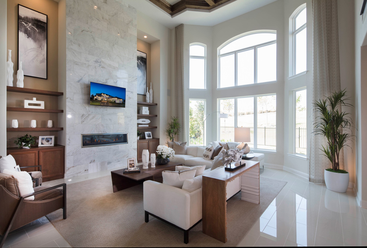 Great room includes a fireplace and a dramatic two-story bay window