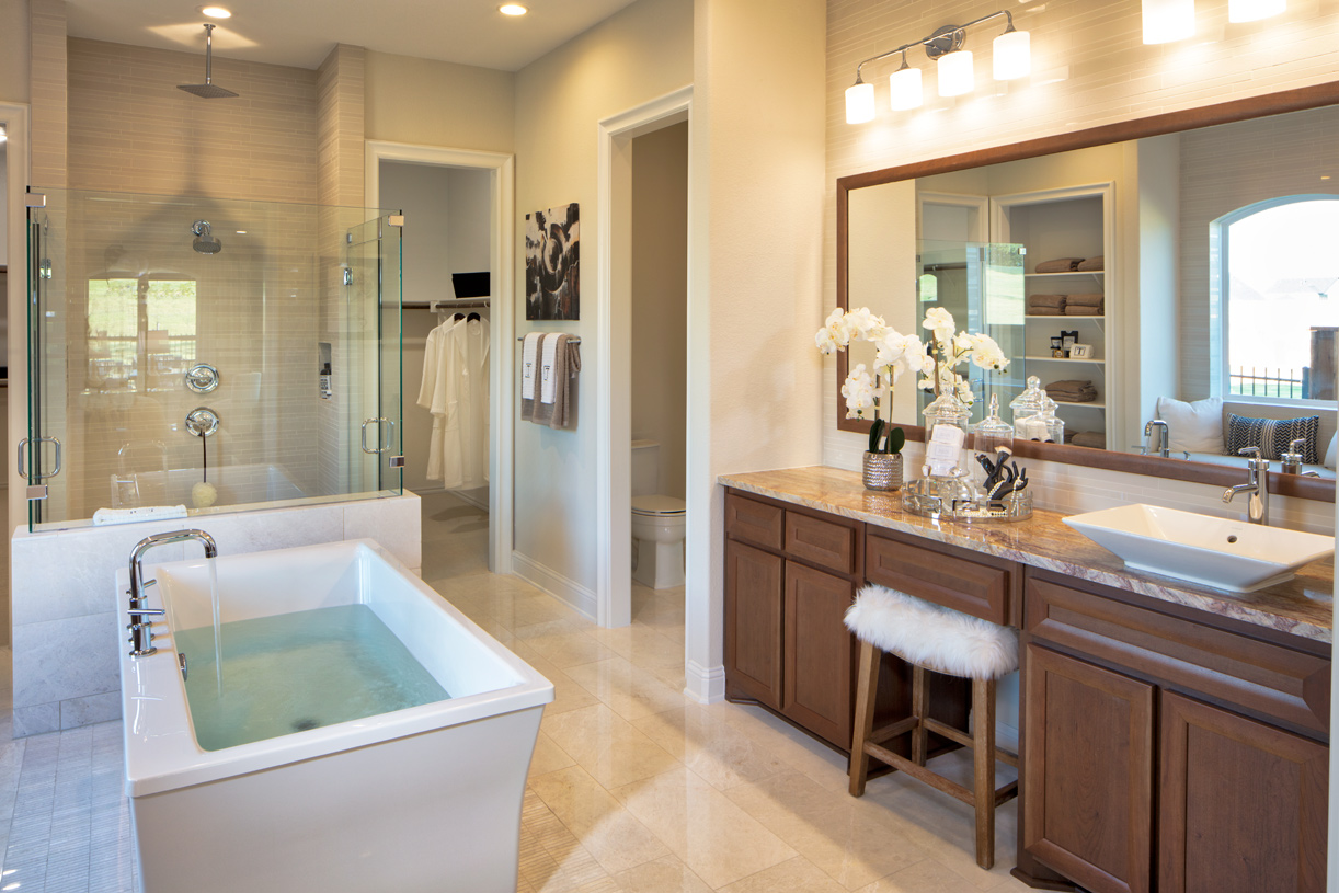 Sumptuous primary bath with dual vanities, shower with seat, and soaking tub