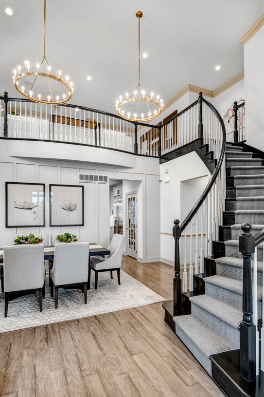Dramatic entry foyer with curved stair and two-story dining room