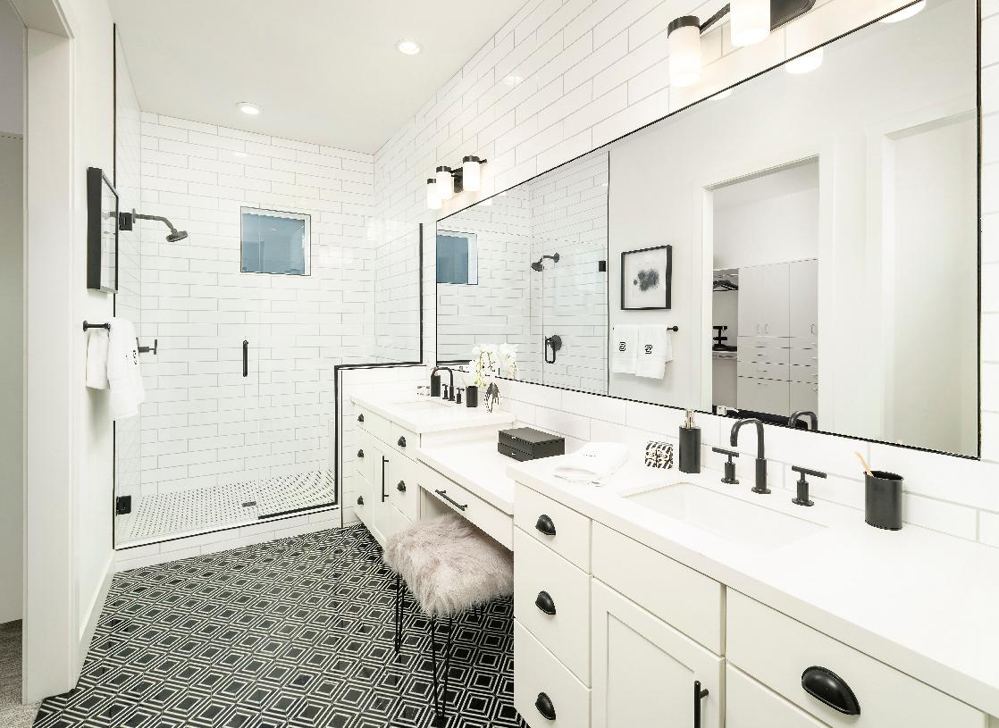 Primary bathroom with black-and-white patterned tile, large walk-in shower, and dual-sink vanity