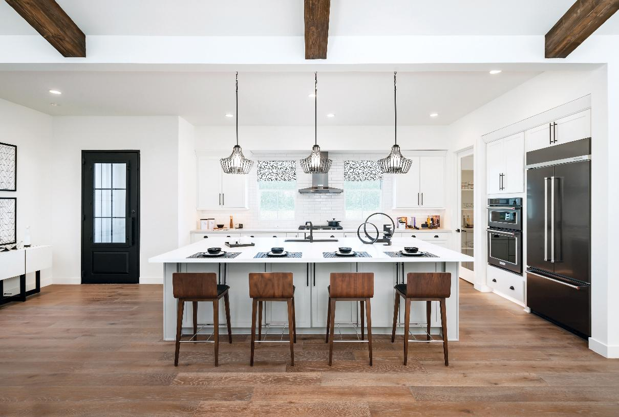 Kitchen with white cabinets, stainless steel appliances, beautiful pendants, and large island with sink