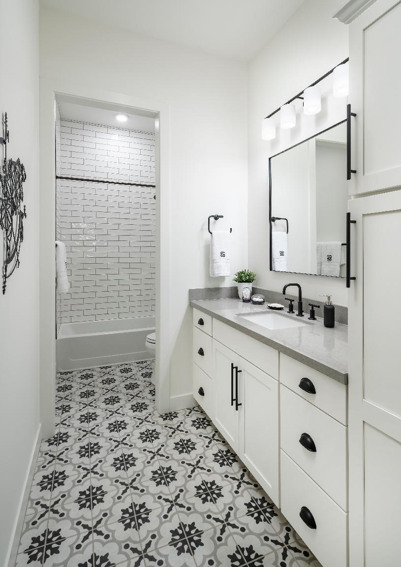 Spacious secondary bathroom with white subway tile in the shower and separate vanity area with patterned tile floor