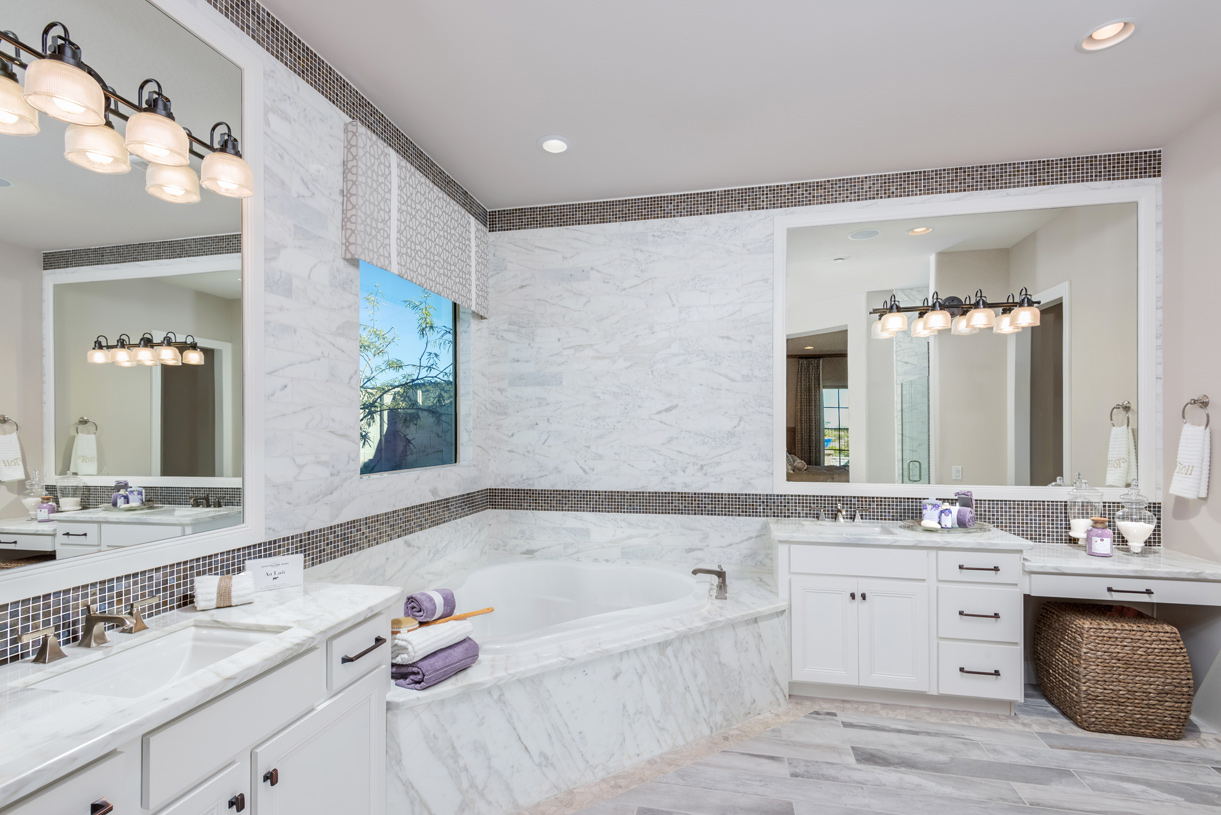Lavish primary bathrooms with dual-sink vanity, large soaking tub, and walk-in shower