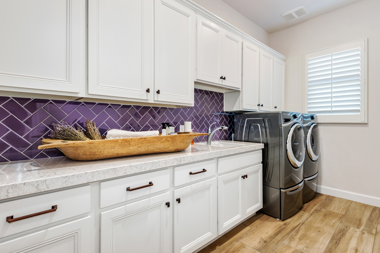 Laundry room with ample countertop and cabinet space