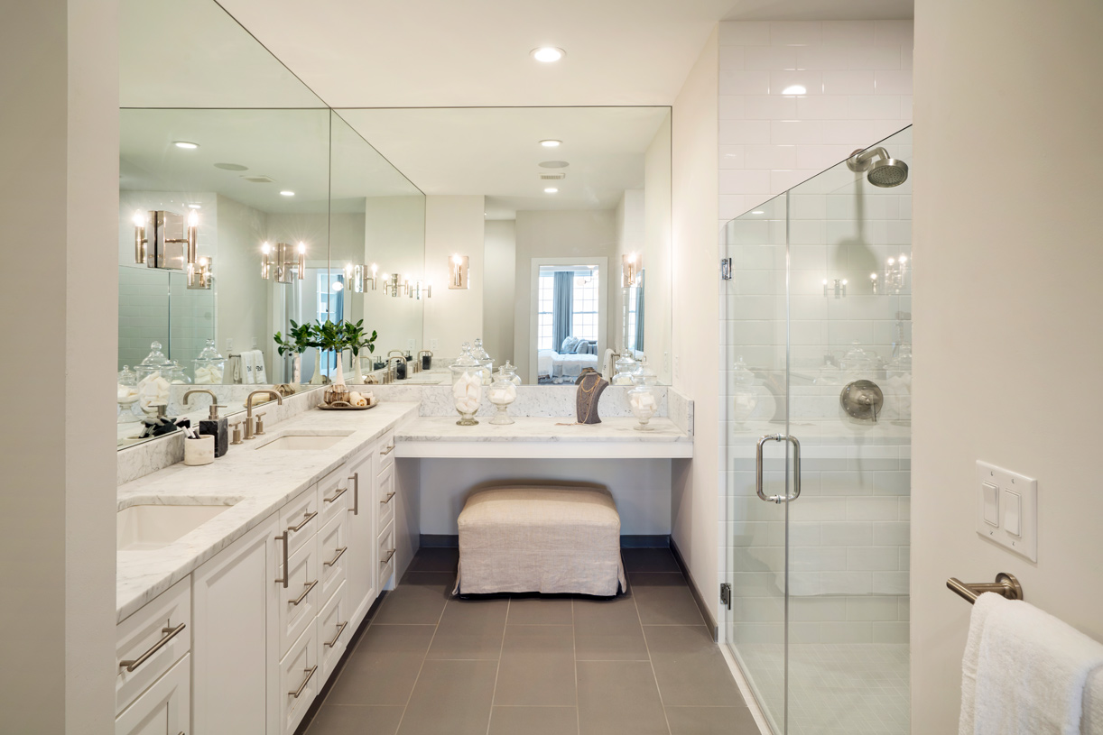The primary bathroom features a dual-sink vanity and large shower