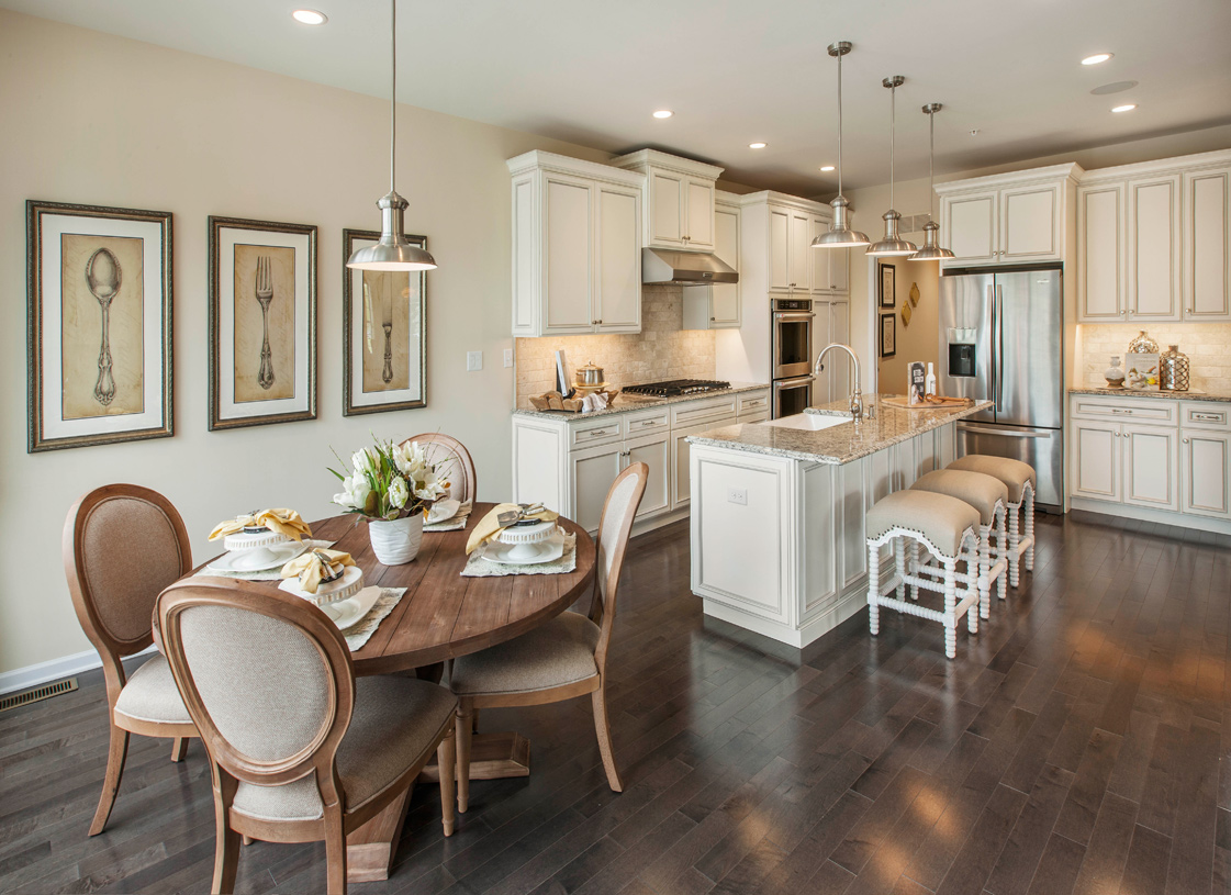 Large center island in kitchen overlooks casual dining area