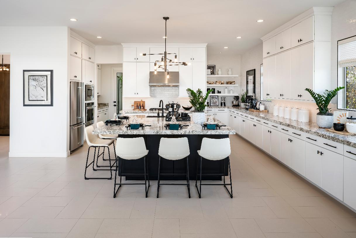 Beautiful kitchen with a large center island, white cabinetry, a tile backsplash, and stainless steel appliances