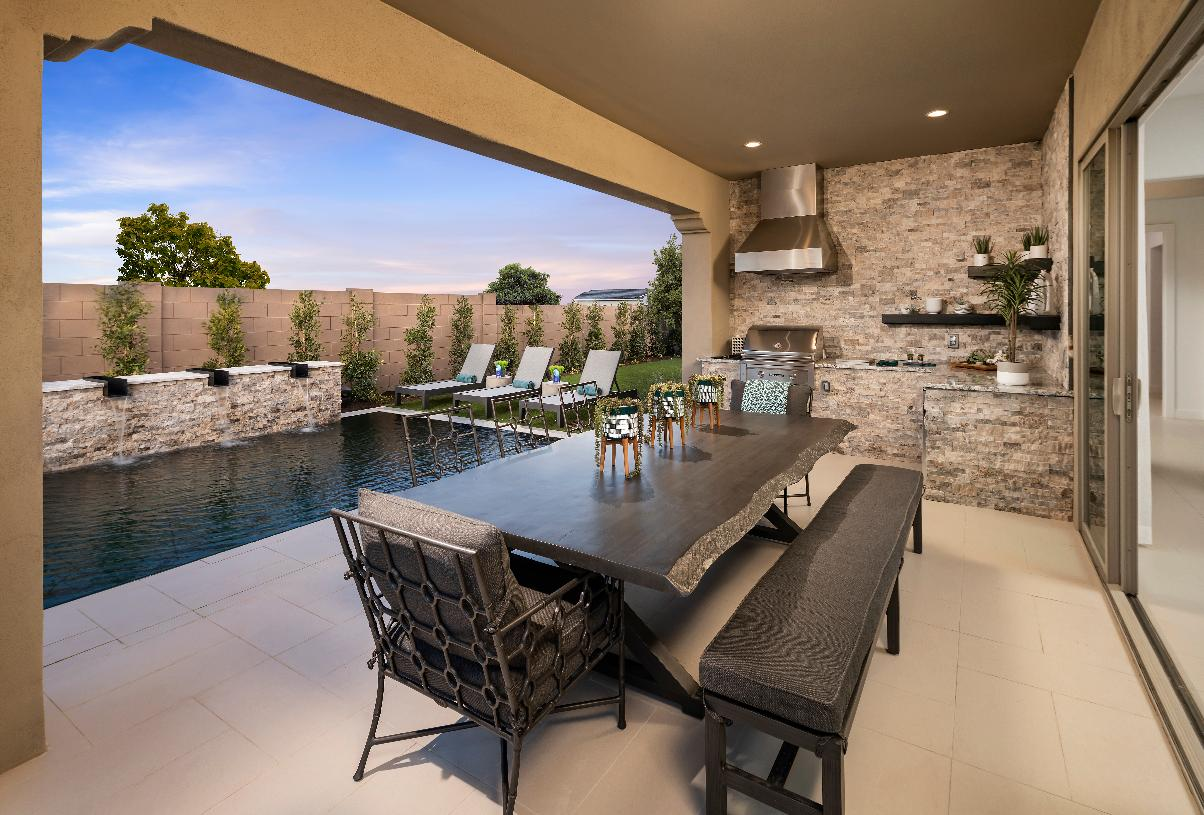 Covered patio with outdoor kitchen and dining are that overlook a serene pool