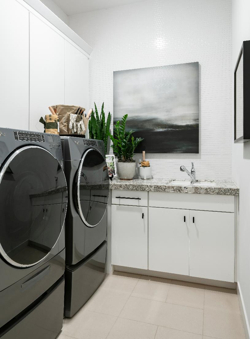 Laundry room with white cabinets, countertop space and a sink