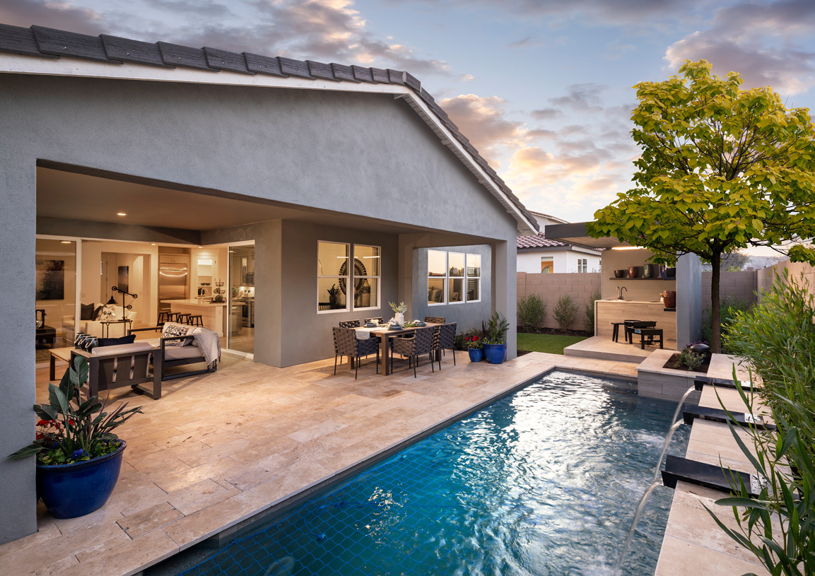 Large rear covered patio overlooks backyard with swimming pool and outdoor kitchen