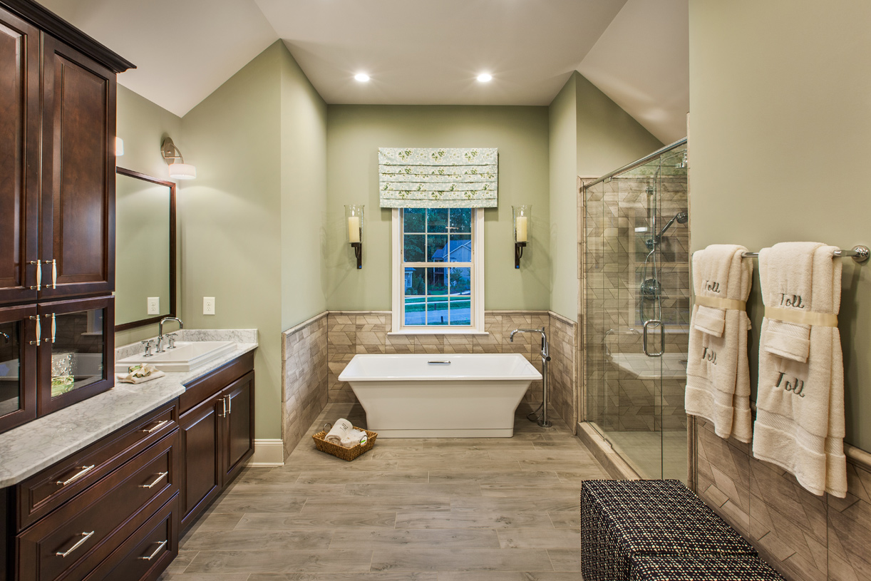 Sumptuous primary bath with cathedral ceiling, dual vanity sinks, luxe soaker tub and separate shower, dressing area, private toilet area, and linen closet