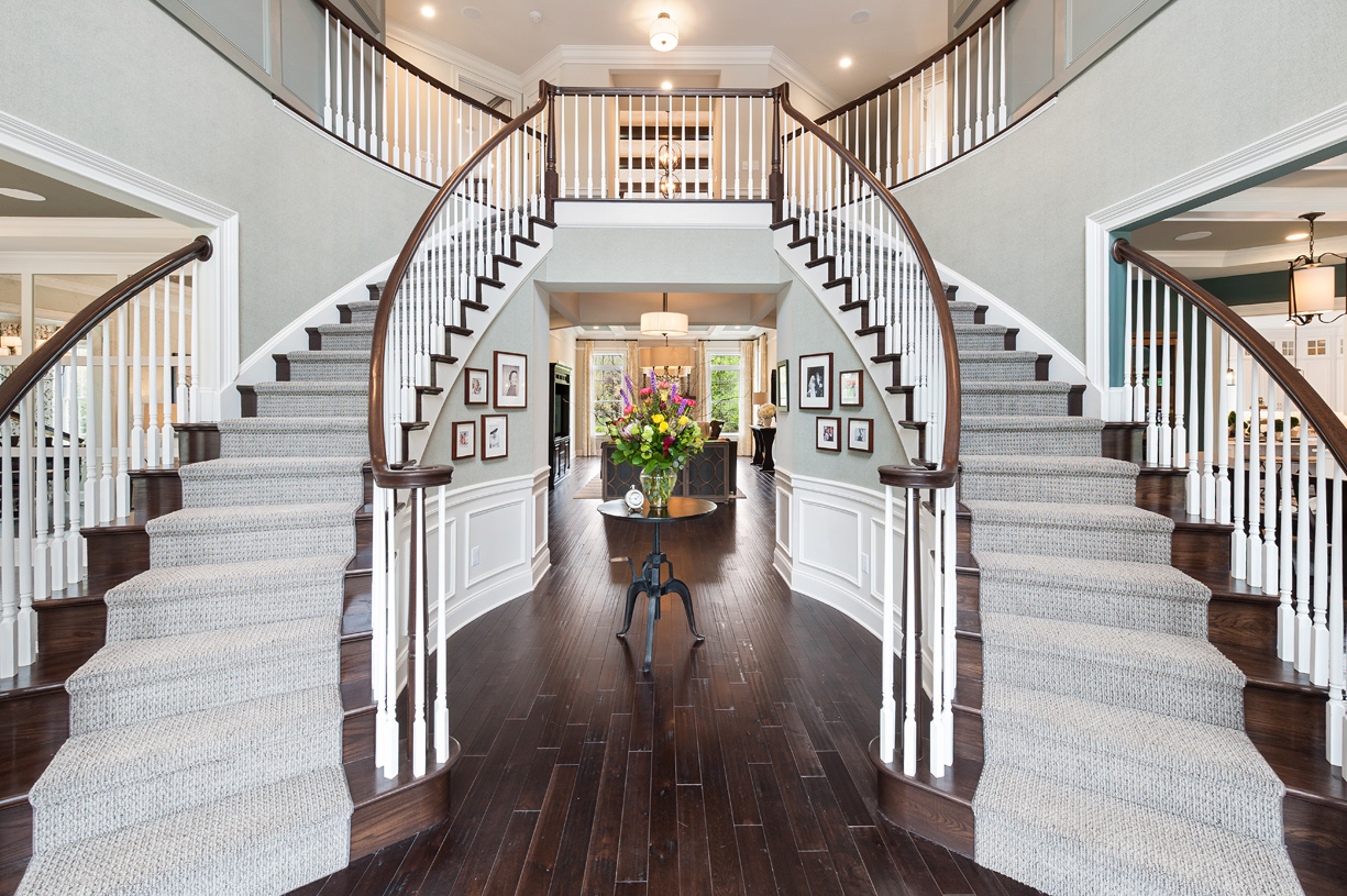 Dramatic entry foyer with dual curved staircases