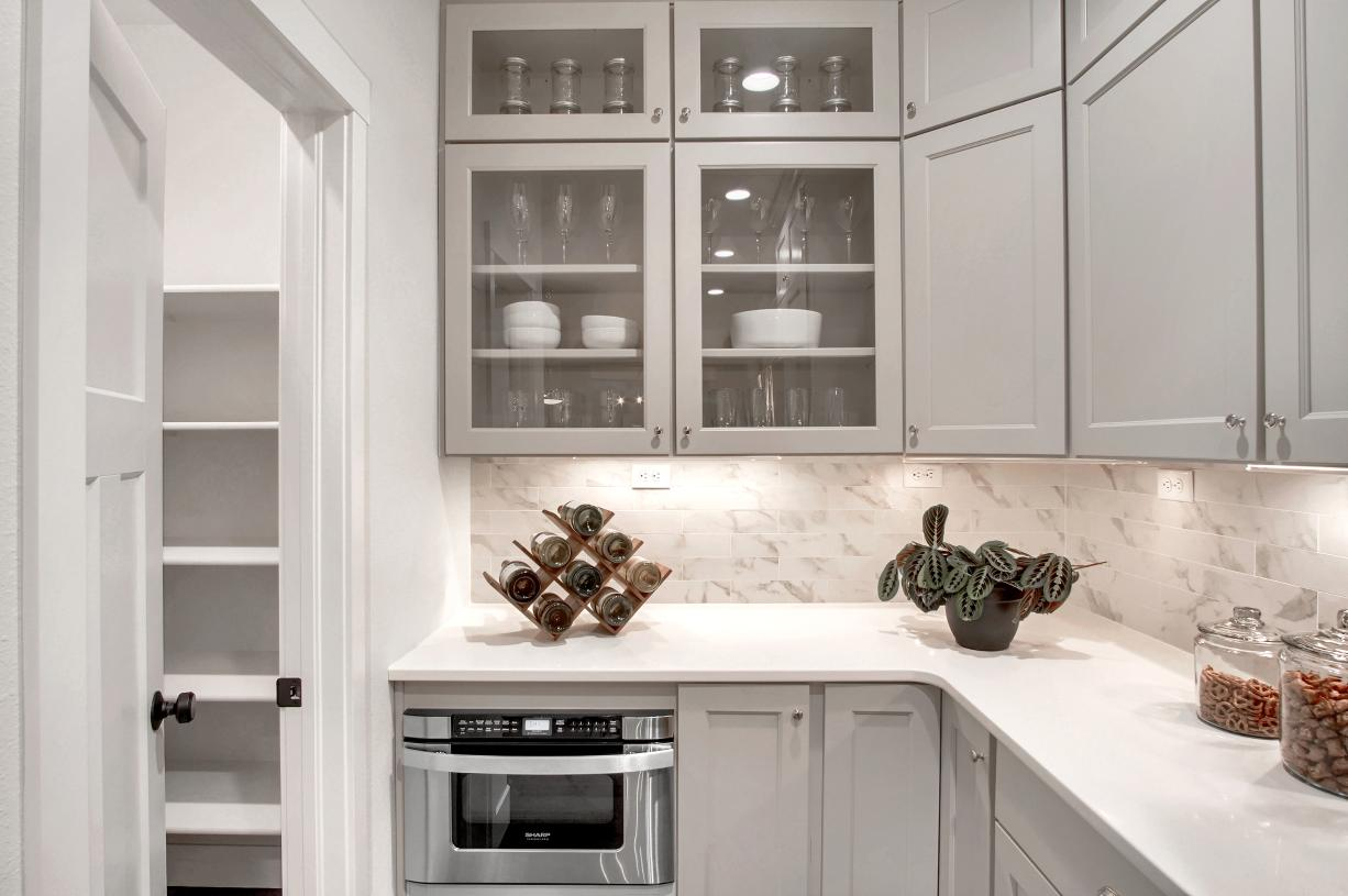 A desirable walk-in pantry can be found tucked at the kitchen