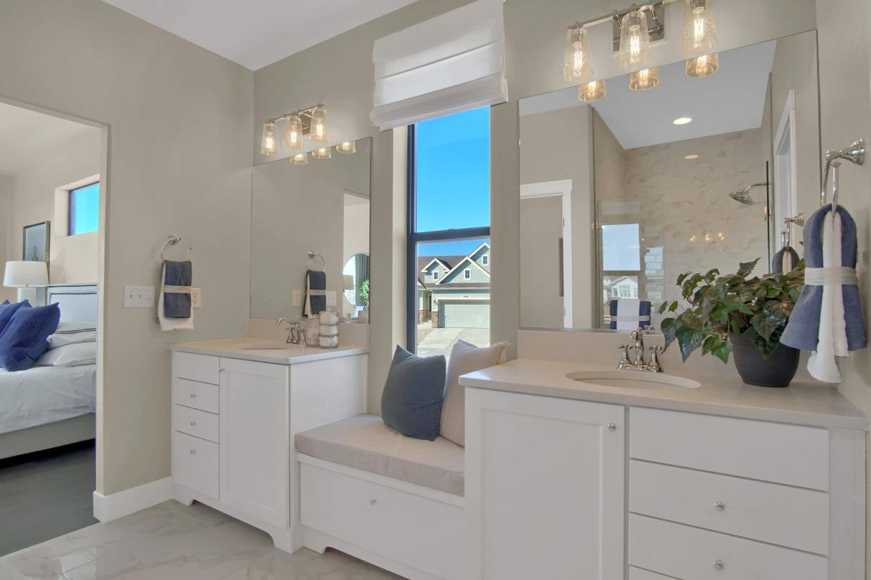 Getting ready in the primary bathroom with dual sink vanity and large walk-in closet