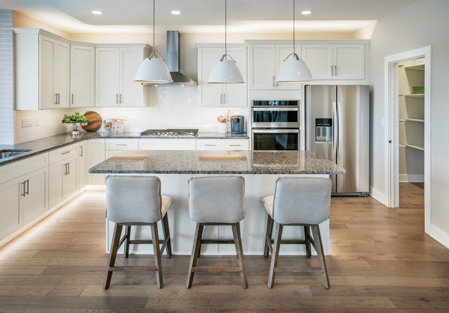 Well-appointed gourmet kitchen with large center island and stainless-steel Whirlpool® appliances