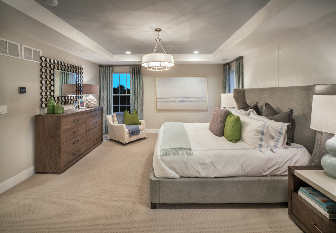 Luxurious primary bedroom suite with elegant tray ceiling and two walk-in closets