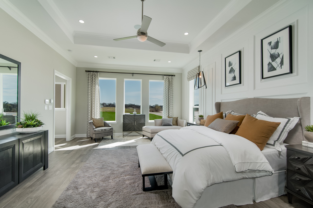 Primary bedroom suite enhanced by a tray ceiling and sitting area