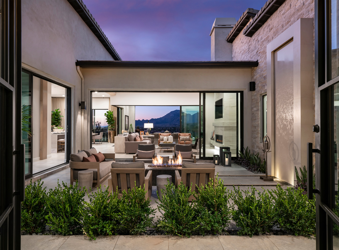 Striking courtyard with views of the great room and resort-style backyard with mountain backdrop