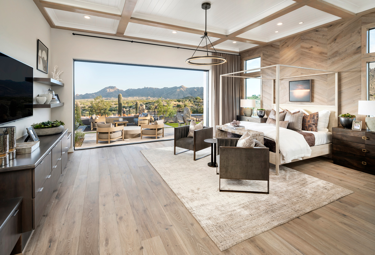 Spacious primary bedroom suite with multi-slide door that opens to resort-style backyard with mountain views