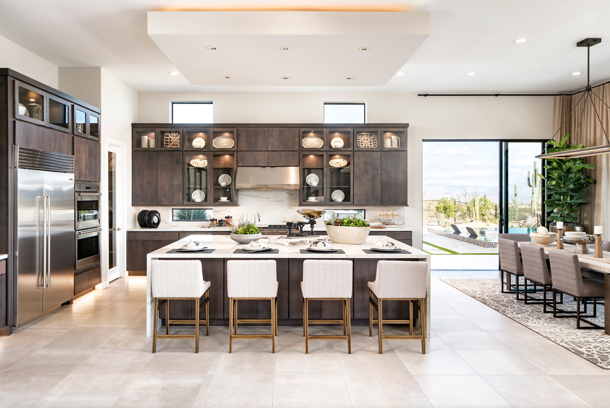 Gourmet kitchen with large center island and adjacent dining space with outdoor views