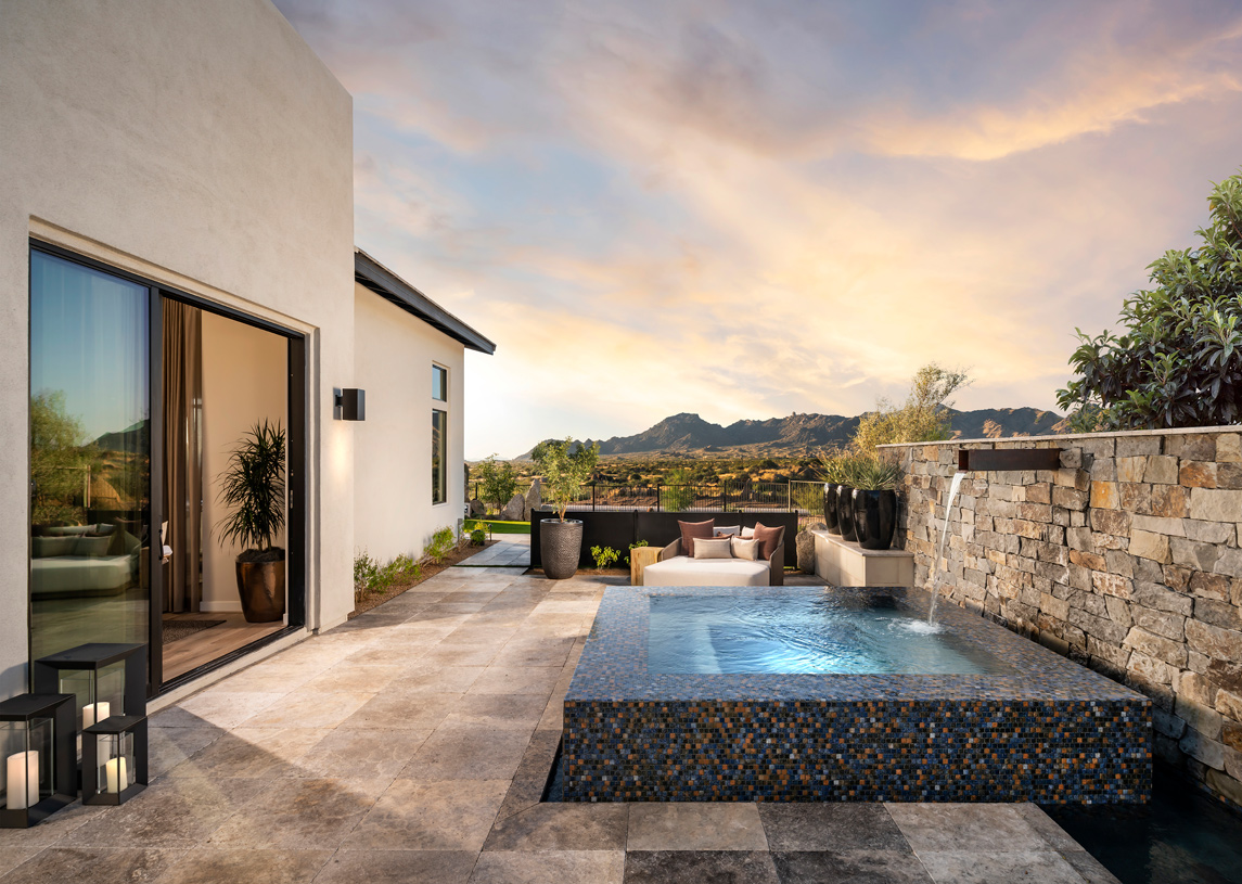 Private outdoor living space off the primary bedroom with spa and sitting area