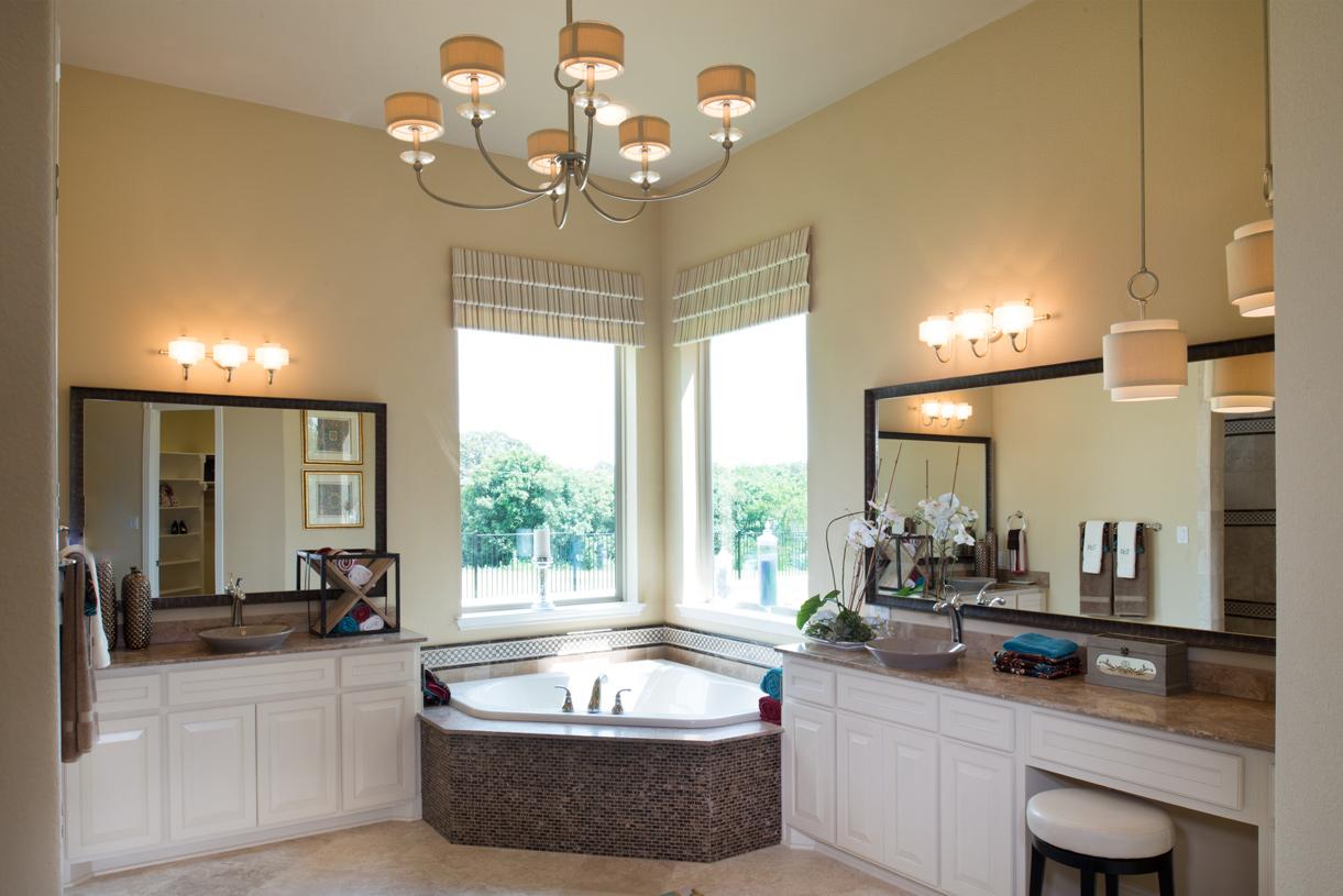 Lavish primary bath with dual vanities and corner tub