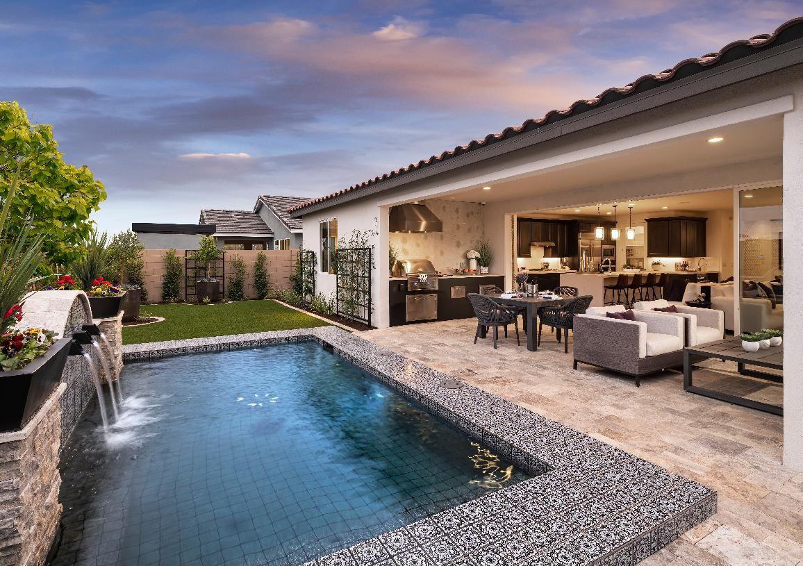Spacious backyard with pool, outdoor kitchen, and dining area