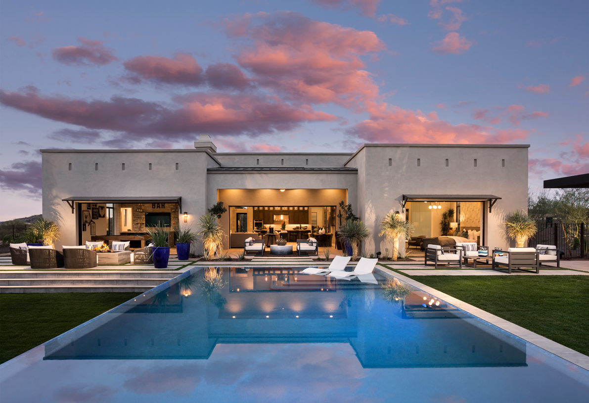 Stunning resort-style backyard with pool, multiple gathering areas, a firepit, and outdoor kitchen