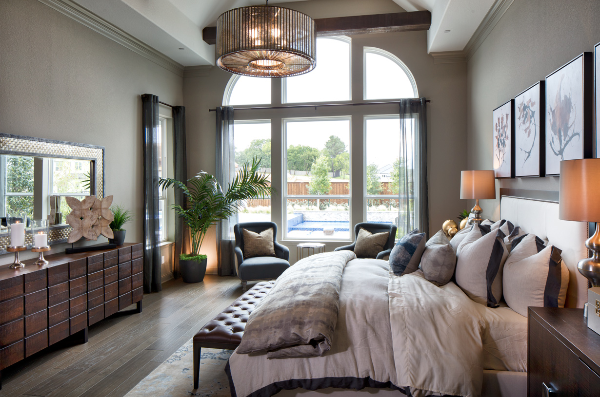 Luxurious primary bedroom suite is enhanced by a vaulted ceiling