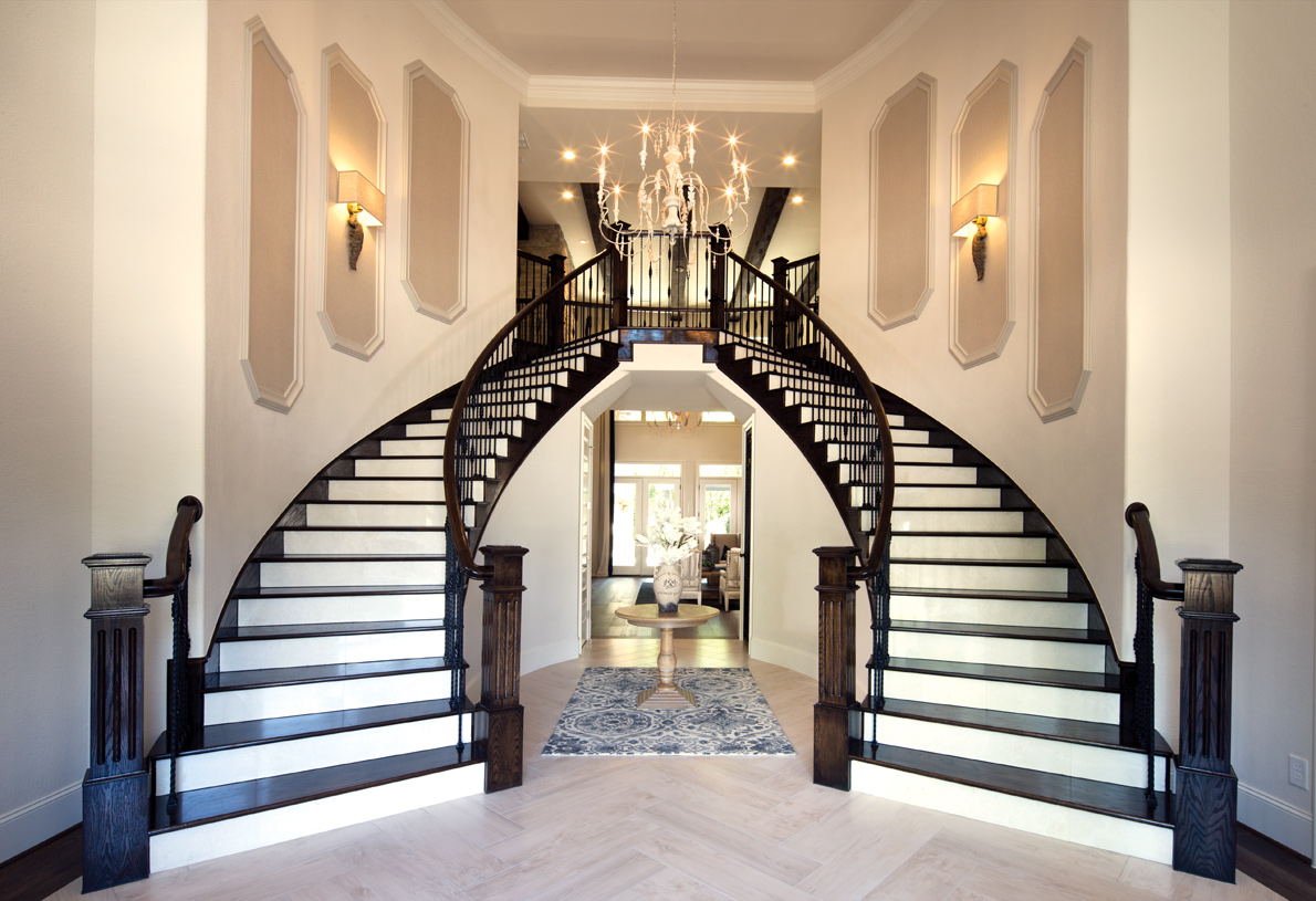 Dramatic dual curved staircases to second-floor hallway overlooks the great room