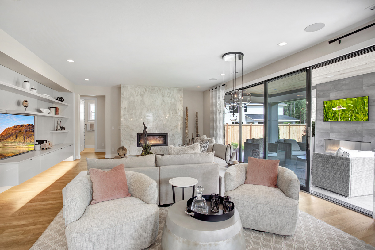 Great room flows to outdoor living through stacked sliding glass doors