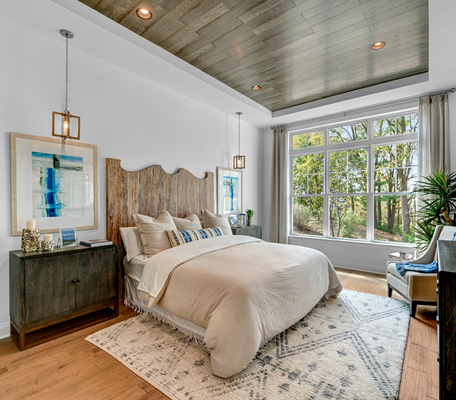 Luxurious first-floor primary bedroom suite with two large walk-in closets