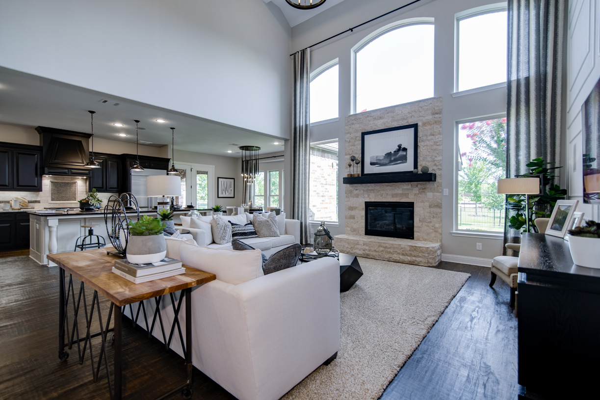 Two-story great room is beneath a barrel-vault ceiling and includes a fireplace