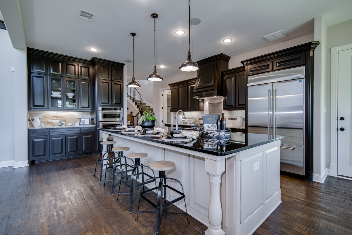 Open kitchen with large center island and adjacent sunlit casual dining area