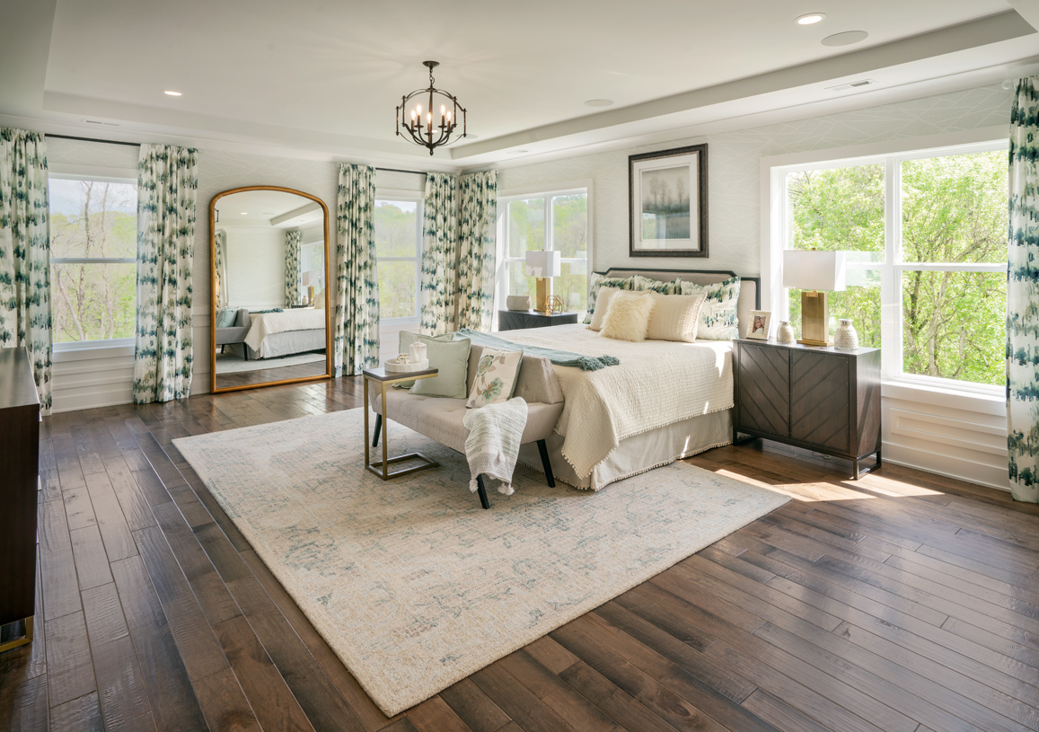 Primary bedroom suite includes tray ceiling and two large walk-in closets